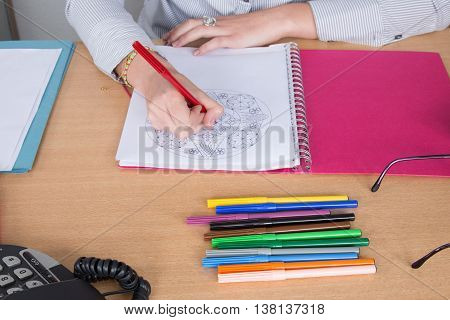 Adult colouring with soft tip pencils at desk