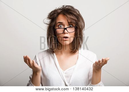 Close up portrait of upset business lady with tousled hair in glasses, mouth opened.