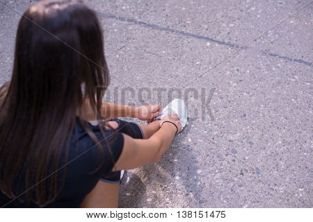 Athlete girl ties running shoes getting ready for jogging