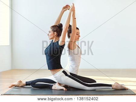 Two Young Women Doing Yoga Asana Eka Pada Rajakapotasana. One Legged King Pigeon