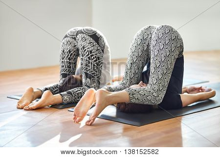 Two Young Women Doing Yoga Asana Easy Plow Pose
