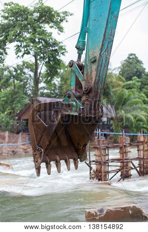 Surat Thane, Thailand-Jun 25 : The excavator machine are use bucket to preparing the land in the Khao-Sok river for building the temporary bridge on Jun 25, 2016 in Surat Thane, Thailand