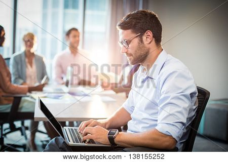 Man using laptop while coworker interacting in the background in the office