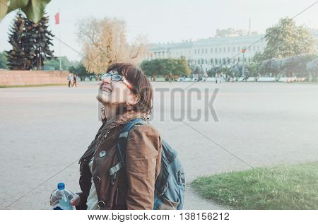 Average age woman traveler in walking on the Field of Mars Marsovo Pole in centre Saint Petersburg Russia. Happy female tourist with glasses blue backpack dressed in casual brown jacket looking up on flowering tree. Europe summer destination.