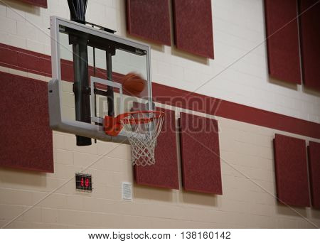 basketball hoop in a school gymnasium with a ball going through it