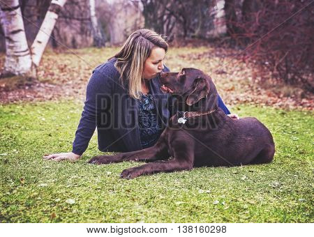 a girl sitting with a dog, a chocolate lab in a park kissing his nose toned with a retro vintage filter instagram app or action effect