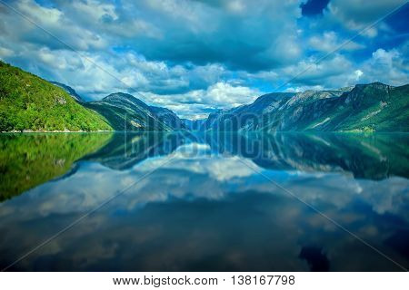 Mountains and clouds reflecting in calm water
