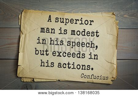 Ancient chinese philosopher Confucius quote on old paper background. A superior man is modest in his speech, but exceeds in his actions. Confucius