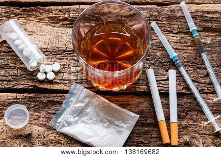 alcohol cigarettes and drugs pernicious habits on wooden background