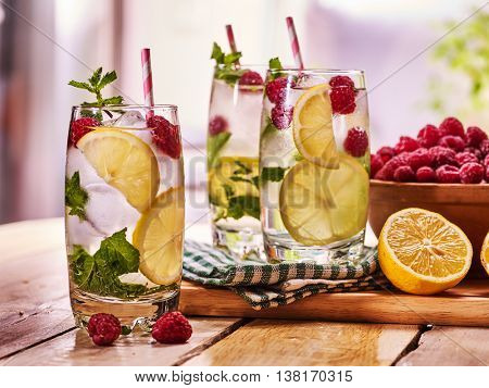 Wooden boards three glasses with alcohol cocktail and ice cubes. Cocktail number hundred twenty four lime cocktail raspberry mohito with straw and mint leaf. Country life. Outdoor. Light background.