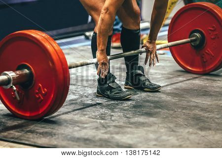 male powerlifter preparing for deadlift of barbell during competition of powerlifting