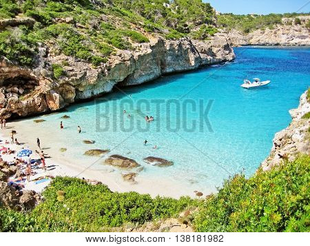 Cala Llombards Majorca Spain - June 22 2008: Bay Calo d'Es Moro - people sunbathing at the beach and swimming in mediterranean sea.