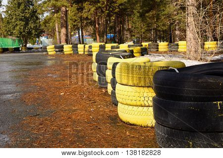 Fragment of a barrier on a carting track made of an old painted tires