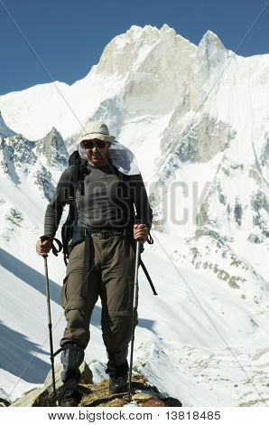 Hiker going along snowy slope in Himalayan mountain
