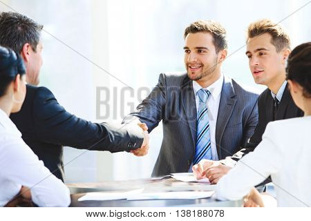 Two businessmen handshaking after striking grand deal