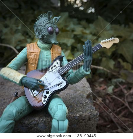 Hasbro Star Wars the Black Series 6 inch action figure of the bounty hunter Greedo playing a guitar outdoors