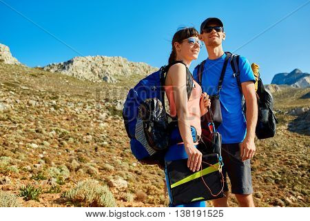female traveler with backpack and a solar panel standing on the trail against sea and blue sky at early morning