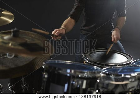 Close Up Of Drummer Playing Drum Kit In Studio