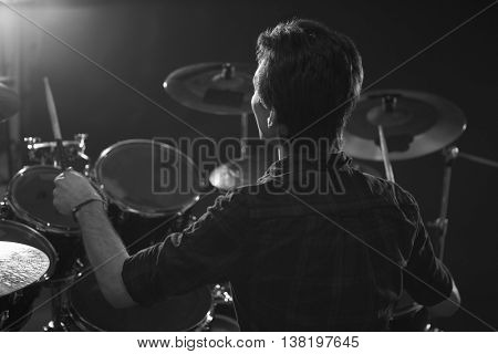 Black And White Shot Of Drummer Playing Drum Kit In Studio