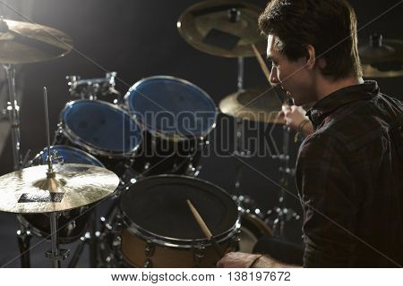 Rear View Of Drummer Playing Drum Kit In Studio