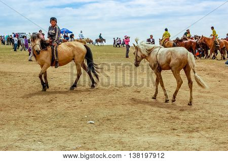 Khui Doloon Khudag Mongolia - July 12 2010: Horseback jockeys at Nadaam (Mongolia's most important festival whose roots lie in Mongolian warrior traditions) horse race near capital Ulaanbaatar.