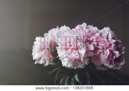 Fresh bunch of pink peonies roses flowers green leaf in glass vase on the window sill white background. Summer time concept. Still life rustic style. Fresh floral home decor.