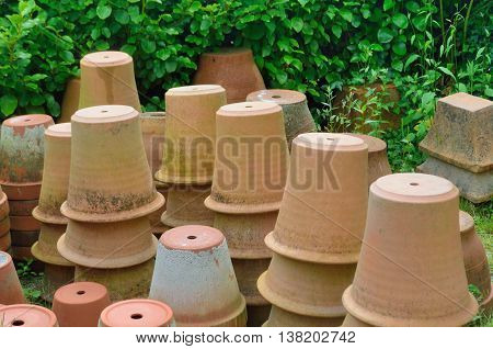 Large group of terracotta gardening pots standing upside down