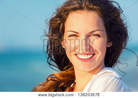 Outdoor portrait of attractive young woman enjoying summer vacation