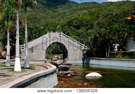 San Ya, Hainan, China: A graceful stone bridge with a high arch spans a stream in the lush tropical gardens at the Sanya Nanshan Temple *