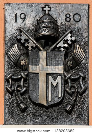 Mount St. Anna Poland - July 7 2016: Arms Pope St. John Paul II on the wall of the Basilica of St. Anne of Mount St. Anna Poland.
