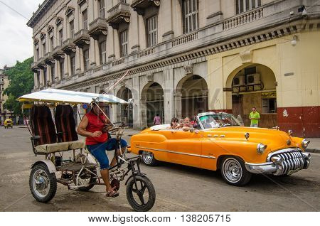 HAVANA, - CUBA , JUNE 17, 2016: A restored 1950 convertible Buick and a pedicab compete for passengers in the historic neighborhood of La Habana Vieja in the Cuban capitol. There are thousands of restored classic cars in Havana
