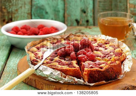 Homemade quark pie with raspberries baked in foil served with green tea closeup