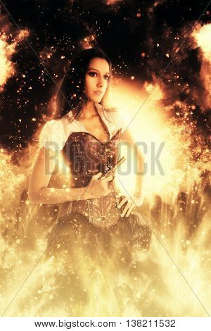 Retro young woman wearing a sexy bustier standing with her hand on her hips holding a gun engulfed in flames and fiery sparks looking to the right of the frame in a conceptual image