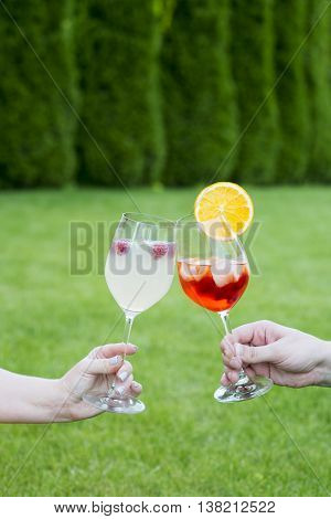 Couple clinking glasses with cocktails oudoors in summertime