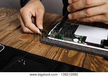 Master uses special tools to fix electronic gadget Unscrewing screws with driver and puts it on magnetic board in front with pincers
