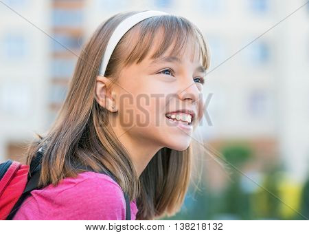 Close-up portrait of smiling girl with schoolbag. Back to school concept.