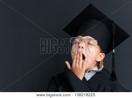 Smart schoolgirl in glasses and academic hat yawning at the blackboard