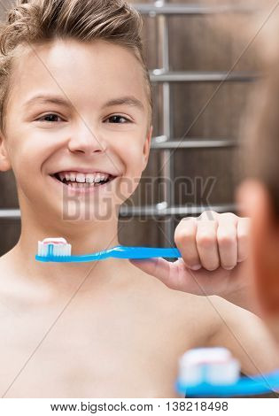 Smiling teen boy brushing teeth in bathroom