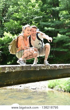 Couple of hikers knelt on a bridge looking at river water