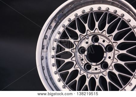 Aluminum metal wheel rim texture. Car alloy wheel, isolated on black background. Classic drive.