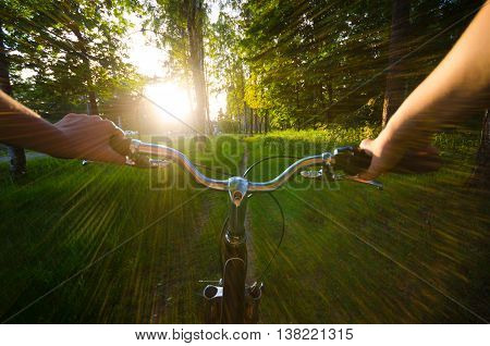 Eye view when girl ride by bycicle in park to sunset. Summer landscape. Sun goes down.