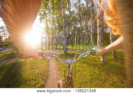 view on girl hands who ride by bycicle in sunset time in the park. Halth evening concept.