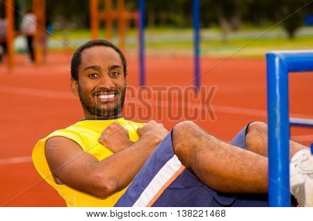 Man wearing yellow shirt and blue shorts lying down on wooden training plank doing situps smiling, orange athletic surface background.