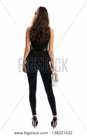 Woman in black outfit. Back view of skinny pants. Luxury heels and precious bracelets. Fashionable apparel for spring.