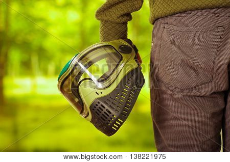 Closeup green and black protection facial mask held by man standing, forest background, paintball concept.
