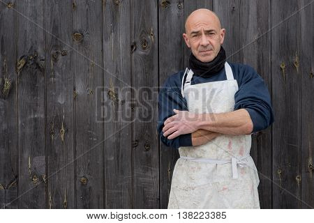Man With Arms Crossed By A Wooden Background