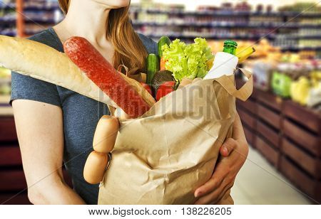 Paper bag with food and drink in woman's hands on background of supermarket