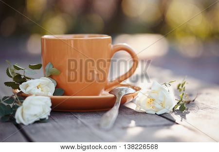 Orange cup with a spoon and an inflorescence of a white dogrose on a wooden table.