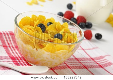 bowl of corn flakes with fresh milk on checkered dishtowel - close up