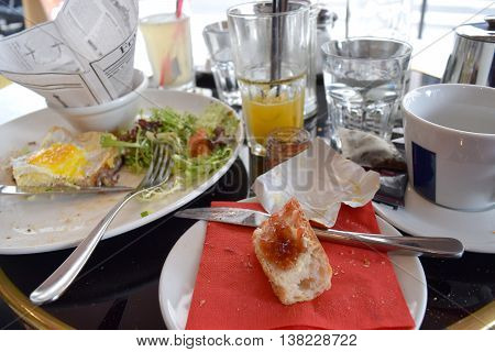 Breakfast at a restaurant/cafe in Paris France overlooking the street. Table with coffee tea orange juice French bread with jam and croque madame.